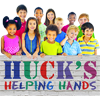 Children holding sign reading Huck's Helping Hands