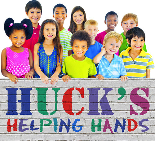 Children standing behind sign reading Huck's Helping Hands